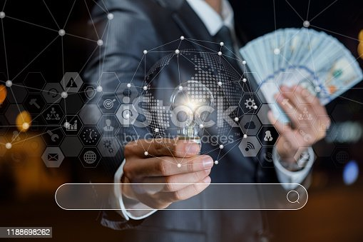 Concept search for ideas to earn money. Businessman showing light bulb and banknotes of dollars on a background search.