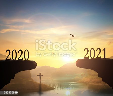 istock 2021 concept: Silhouette of year 2021 and cross  on mountain  with  sunset  background 1285475619
