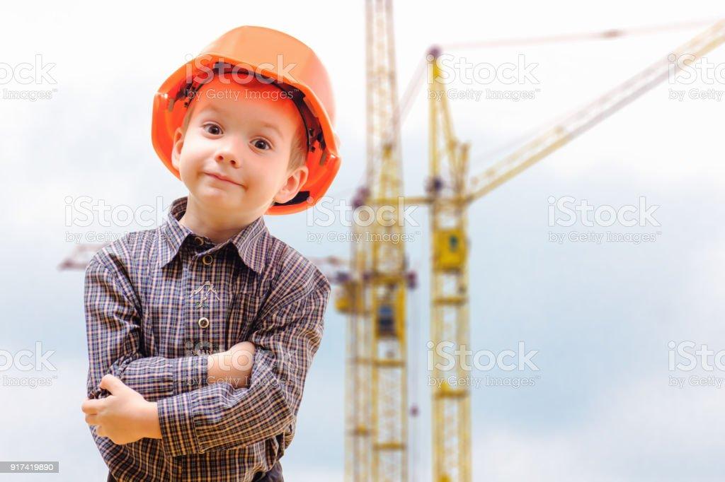 Conceito, menino pequeno em um capacete, olhando o canteiro de obras com guindastes - foto de acervo