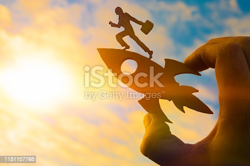 istock Concept start up. Silhouette of a businessman with a briefcase on a rocket holds the hand of a man 1151157765