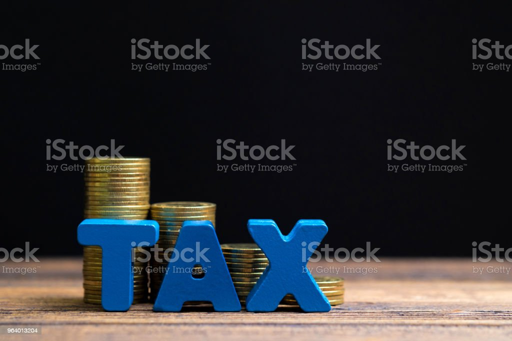 TAX concept. TAX alphabet with stack of coin on wooden working table in dark background, business and financial concept. - Royalty-free Accountancy Stock Photo