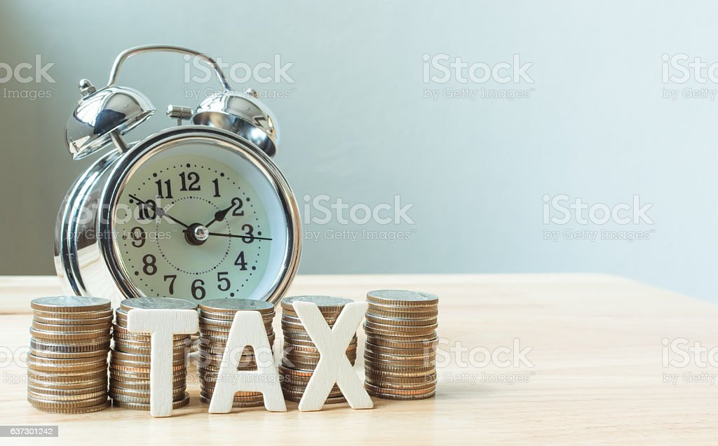 Concept tax time and alarm clock with coins stack stock photo