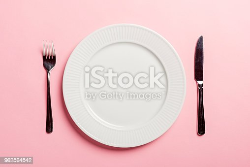 An  idea to illustrate diet. A studio shot of  a dinner plate with a knife and fork. Colour, overhead view with a pink background for lots of copy space.