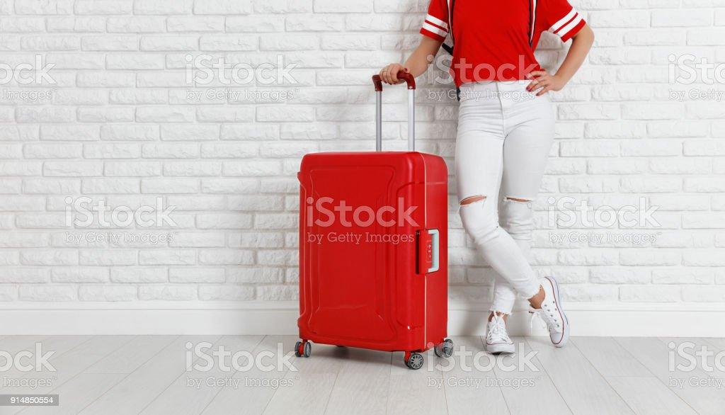 Konzept-Reise- und Tourismusbranche. Beine des Mädchens mit einem roten Koffer in der Nähe von weißen leeren Wand – Foto