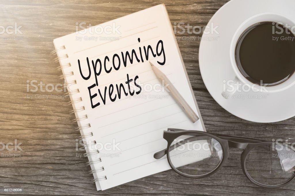 Message de prochains événements de concept sur portable avec lunettes, crayon et café tasse sur la table en bois. photo libre de droits