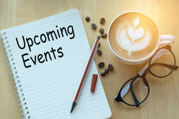 Concept Upcoming Events message on notebook with glasses, pencil and coffee cup on wooden table. stock photo