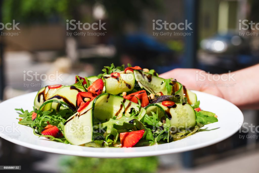 Concept: vegetarian food, nutrition, diet. Salad with arugula, strawberries and cucumber. stock photo