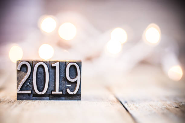 2019 Concept Vintage Letterpress Type Theme The word 2019 written in vintage metal letterpress type on a bokeh light and wooden background. 2019 stock pictures, royalty-free photos & images