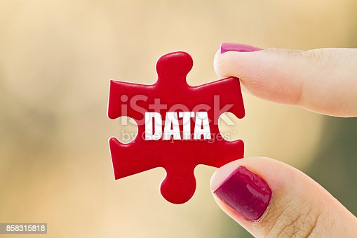 Young woman hand holding the last piece of jigsaw puzzle. DATA concept.