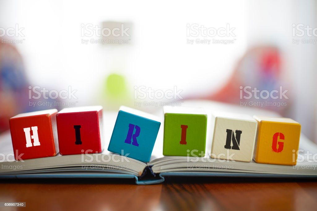 HIRING Concept with six building blocks on book stock photo