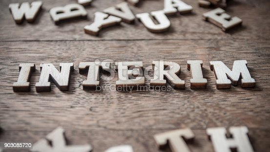 istock concept wooden word on wooden table - Interim 903085720