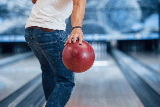 Conception of bowling. Rear particle view of man in casual clothes in the club stock photo