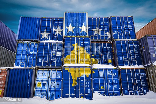 The national flag of Kosovo  on a large number of metal containers for storing goods stacked in rows on top of each other. Conception of storage of goods by importers, exporters