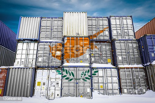 The national flag of Cyprus  on a large number of metal containers for storing goods stacked in rows on top of each other. Conception of storage of goods by importers, exporters