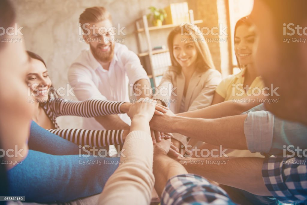 Conception of successful teambuilding. Cropped close up photo of partners putting their hands on top of each other at the workstation, wearing casual clothes, smiling stock photo