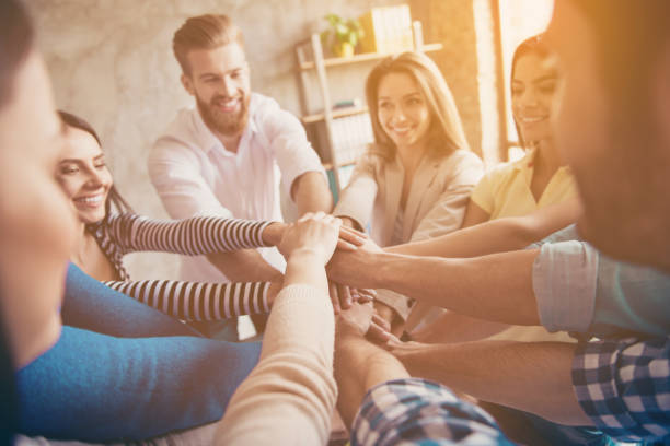 conception of successful teambuilding. cropped close up photo of partners putting their hands on top of each other at the workstation, wearing casual clothes, smiling - public celebratory event stock photos and pictures