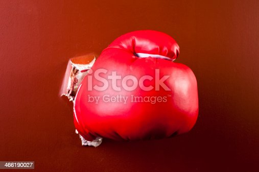 160558362 istock photo Concepts: Boxing glove punches through wall. Fist, conflict. 466190027