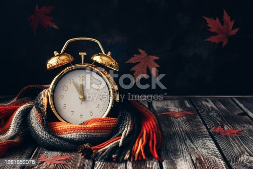 Conceptual autumn composition. Gold alarm clock wrap knitted scarf on a wooden vintage table and decorated with maple leaves. Selective focus, copy space