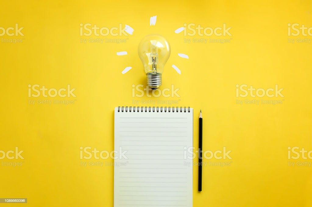 Flat lay of light bulb and empty memo pad and pencil on yellow...