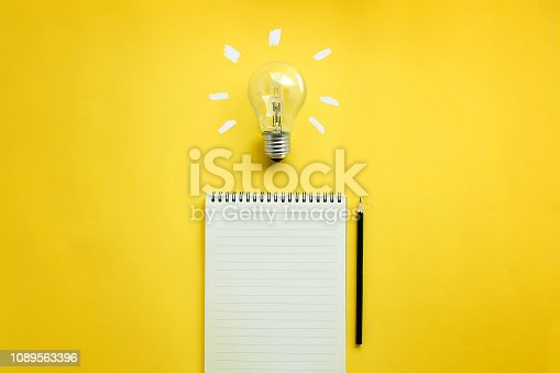 Flat lay of light bulb and empty memo pad and pencil on yellow background with texts.