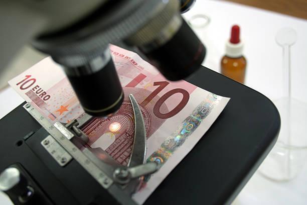 Konzeptionelle-Suche nach falsche euro banknote mit einem Mikroskop – Foto