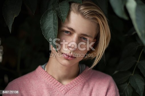 846124694 istock photo Conceptual closeup portrait of a young handsome man with a hairstyle in green leaves 846125108