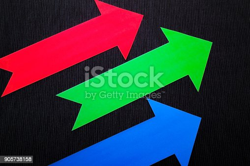 157434064 istock photo conceptual colored arrows on the dark blue texture background 905738158