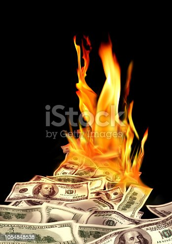 Conceptual finance image of burning pile of money, dollar bills, and fire flames in black background
