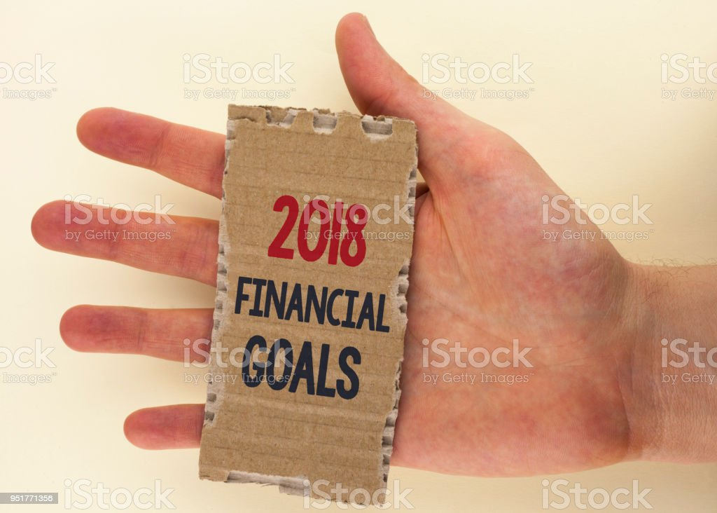 Conceptual hand writing showing 2018 Financial Goals. Business photo text New business strategy earn more profits less investment written on Tear Cardboard Piece on the plain background Hand. stock photo