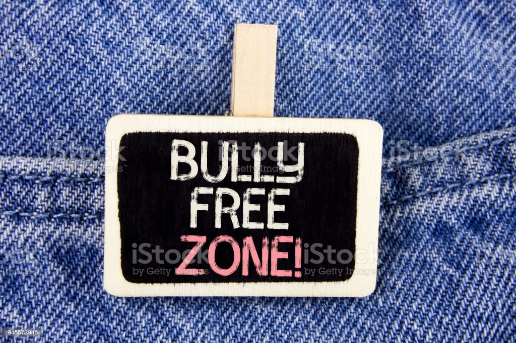Conceptual hand writing showing Bully Free Zone Motivational Call. Business photo text creating abuse free school college life written on Wood Piece on the Jeans background. stock photo