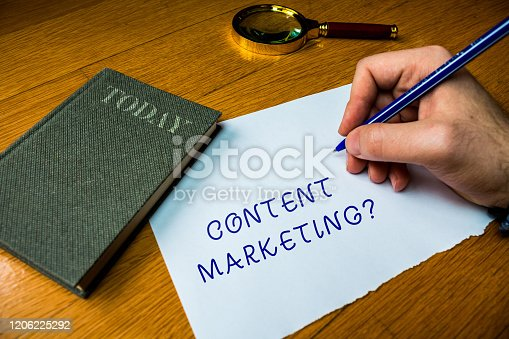 istock Conceptual hand writing showing Content Marketing question. Business photo text involves creation and sharing of online material Man writing document wood table magnifying glass electronic device. 1206225292