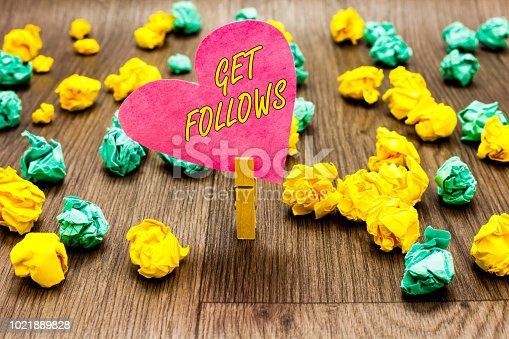 istock Conceptual hand writing showing Get Follows. Business photo text person who imitates copies or takes as model ideal person Clothespin holding pink paper heart crumpled papers several tries. 1021889828
