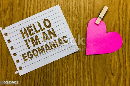 Conceptual hand writing showing Hello I am An Egomaniac. Business photo showcasing Selfish Egocentric Narcissist Self-centered Ego Yellow woody deck word with white page paper clip grip heart