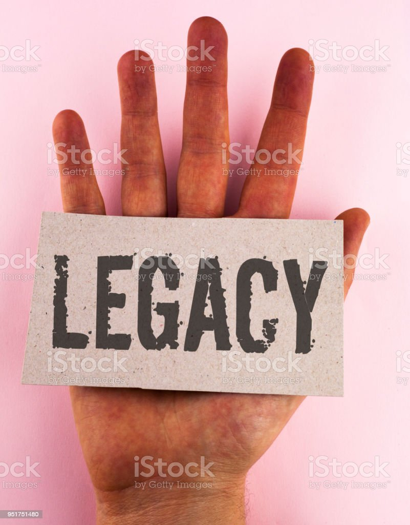 Conceptual hand writing showing Legacy. Business photo text Transmitted Received from an ancestor Money Properties given by will written on Cardboard Piece placed on the Hand on plain background. stock photo