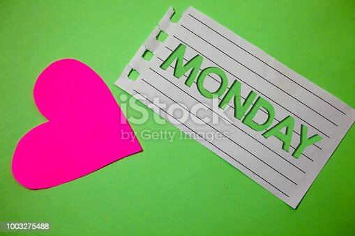 istock Conceptual hand writing showing Monday. Business photo showcasing First day of the week Back to work Weekend is over Wakeup Early Small paper drawing heart green background remember message. 1003275488