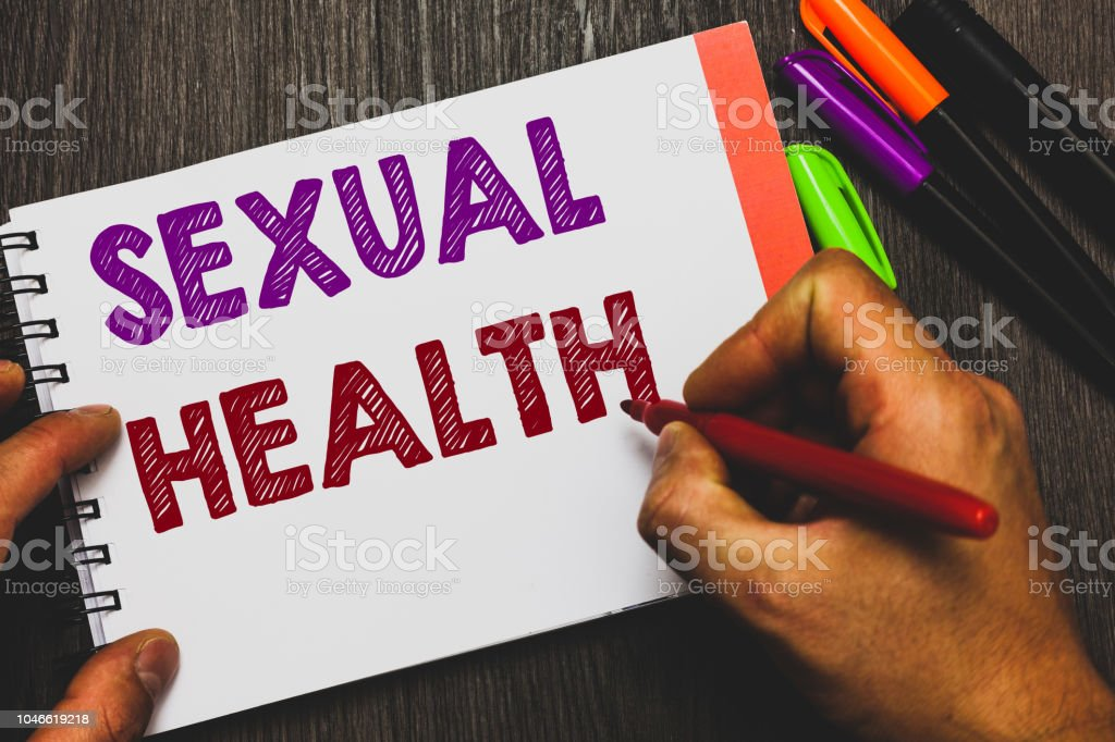 Conceptual hand writing showing Sexual Health. Business photo text Healthier body Satisfying Sexual life Positive relationships Man holding notebook paper communicating ideas Wooden background. stock photo