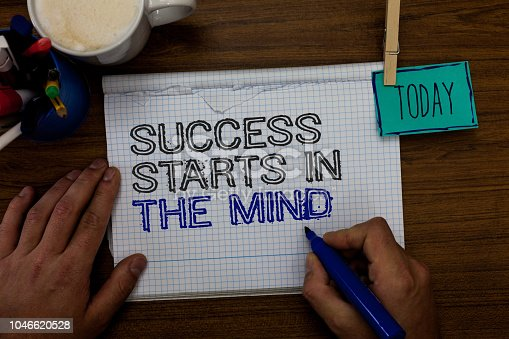 Conceptual hand writing showing Success Starts In The Mind. Business photo showcasing Have positive thoughts accomplish what you want Hand hold pen paper clip written notepad pen case coffee mug