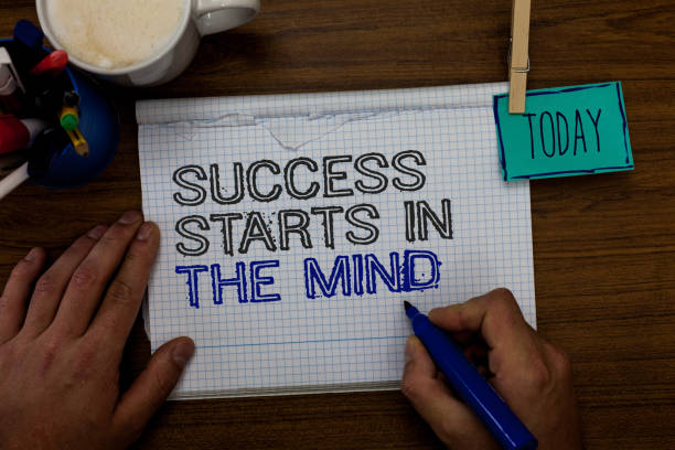 Conceptual hand writing showing Success Starts In The Mind. Business photo showcasing Have positive thoughts accomplish what you want Hand hold pen paper clip written notepad pen case coffee mug. stock photo
