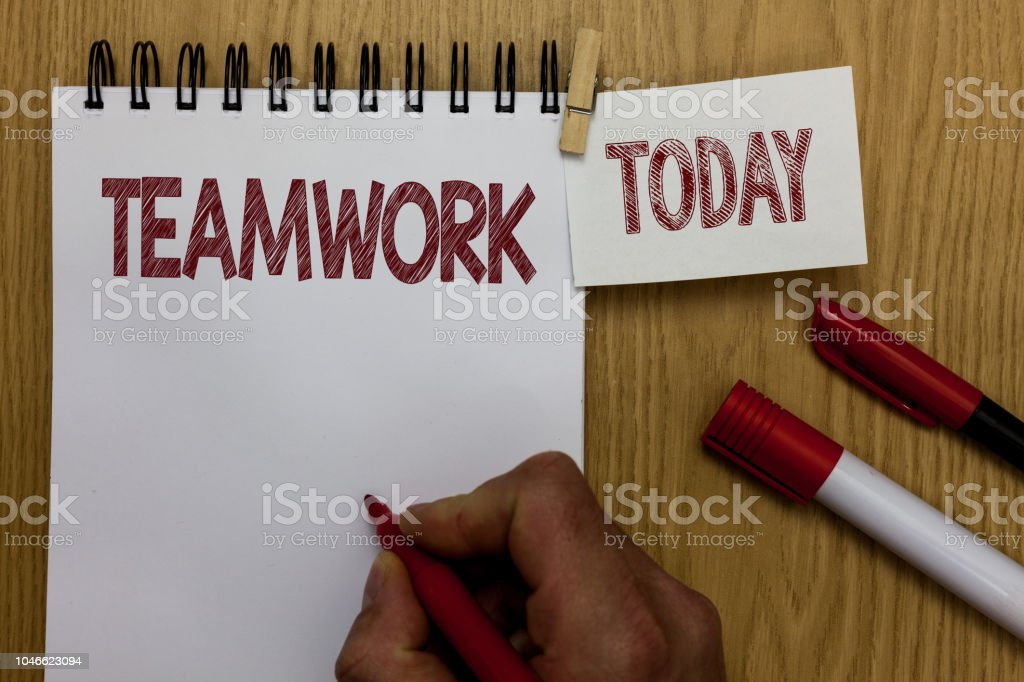 Conceptual hand writing showing Teamwork. Business photo text Group of people who work together as one and with the same aim Man holding marker notebook wooden table for today coffee cup. stock photo