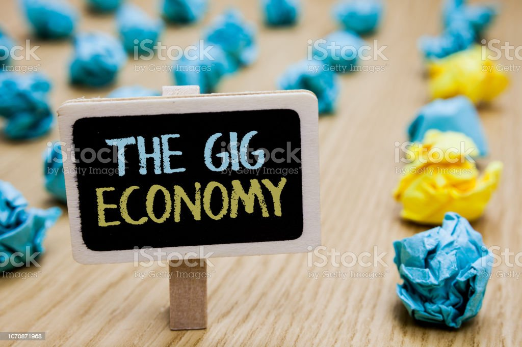 Conceptual hand writing showing The Gig Economy. Business photo text Market of Short-term contracts freelance work temporary poster board with blurry paper lobs laid serially mid yellow lob. stock photo
