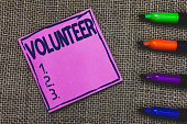 istock Conceptual hand writing showing Volunteer. Business photo showcasing Person who freely offers to take part in something Charity Purple Paper Important reminder Markers Jute background. 1056068310