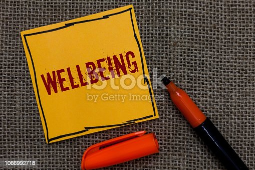 istock Conceptual hand writing showing Wellbeing. Business photo showcasing A good or satisfactory condition of existence including health Orange paper Marker Communicate ideas Jute background. 1066992718
