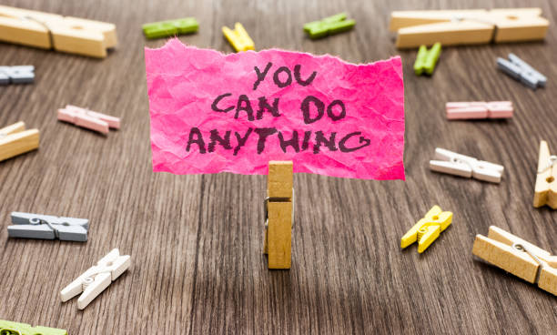 Conceptual hand writing showing You Can Do Anything. Business photo showcasing Motivation for doing something Believe in yourself Paperclip hold pink note with texts many clips wooden floor. stock photo