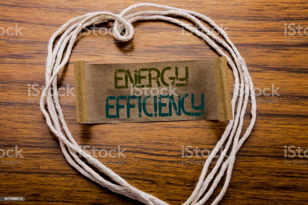 Conceptual hand writing text caption Energy Efficiency. Business concept for Electricity Ecology written on sticky note paper on the dark wooden background. With heart meaning love or adoration. stock photo