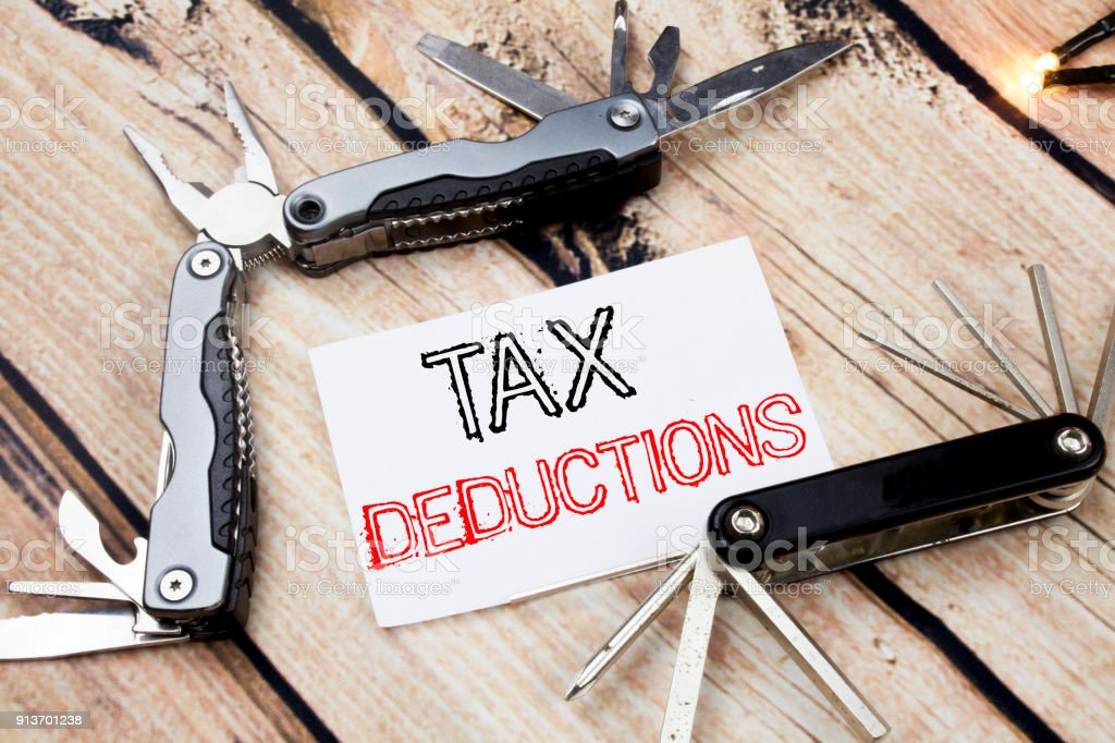 Conceptual hand writing text caption inspiration showing Tax Deductions. Business concept for Finance Incoming Tax Money Deduction Written on sticky note wooden background with pocket knife stock photo