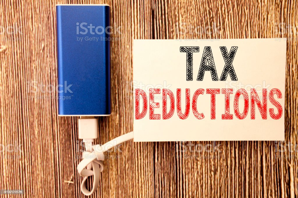 Conceptual hand writing text caption inspiration showing Tax Deductions. Business concept for Finance Incoming Tax Money Deduction written on sticky note old wood wooden background with power bank stock photo