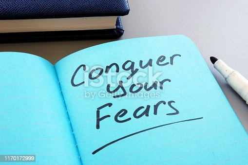 Conceptual hand writing text showing Conquer your fears
