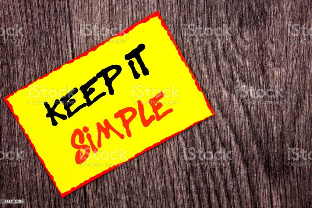 Conceptual hand writing text showing Keep It Simple. Concept meaning Simplicity Easy Strategy Approach Principle written on Yellow Sticky Note Paper on the wooden background. stock photo