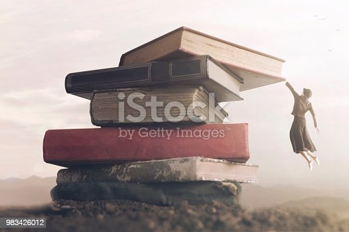 istock conceptual image a brave woman climbing a pile of books to reach the top 983426012