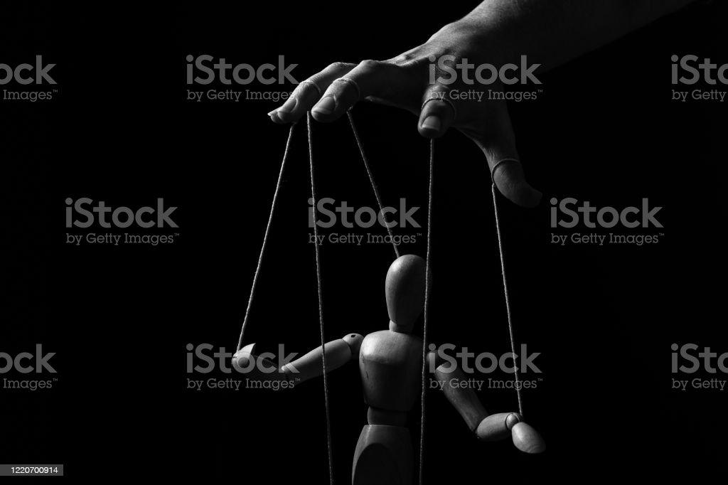 Conceptueel beeld van een hand met koorden op vingers om een marionet in monochroom te controleren - Royalty-free Aan elkaar bevestigd Stockfoto